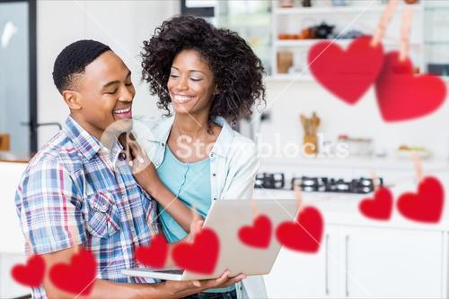 Composite image of red hanging hearts and smiling couple using laptop