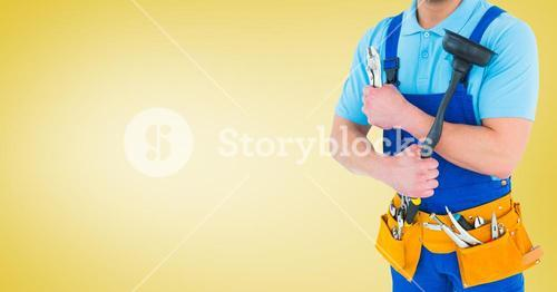 Handy man standing with tools against yellow background