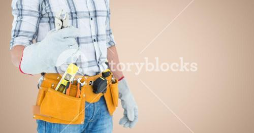 Handy man standing with tools against beige background