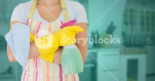 Cleaner standing with spray bottle in kitchen