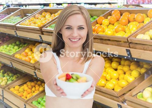 Woman with fruit bowl in supermarket