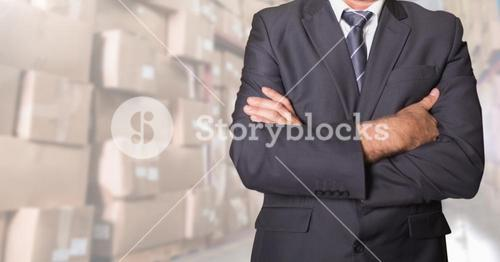 Businessman standing with his arms crossed at warehouse