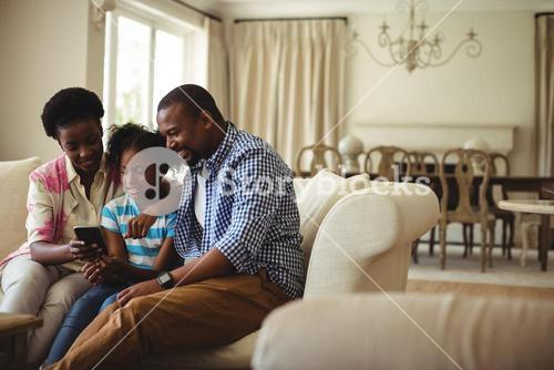 Family using mobile phone in living room