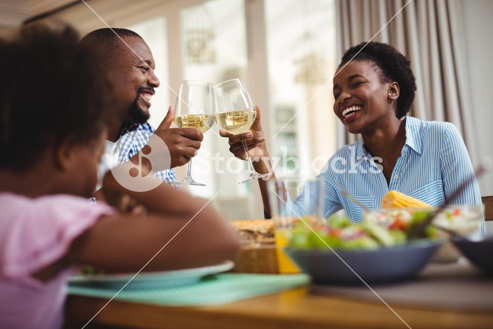 Family toasting glasses of wine while having meal on dining table