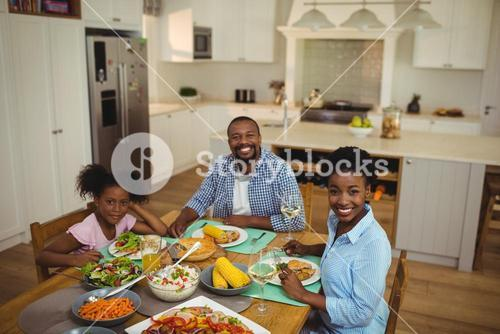 Portrait of family having meal on dinning table at home