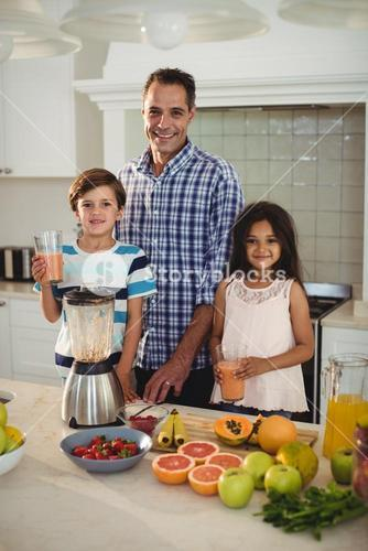 Portrait of father and kids holding glass of smoothie