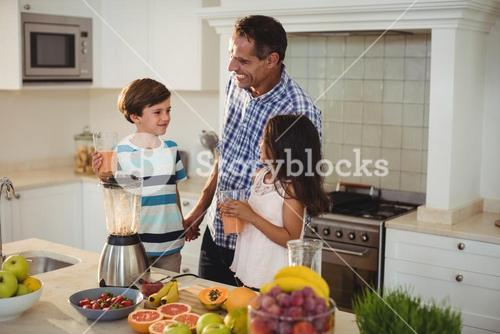 Father and kids holding glass of smoothie