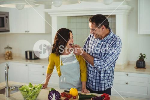 Man feeding woman in the kitchen