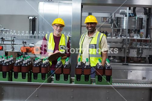 Portrait of two factory workers monitoring cold drink bottles in the plant