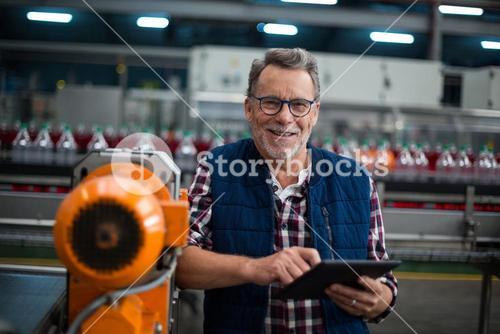 Portrait of smiling factory worker standing with a digital tablet in the factory