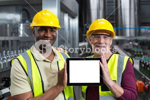 Portrait of factory workers holding digital tablet in the plant