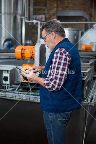 Factory worker working on digital tablet in the factory