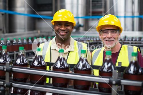 Smiling factory workers monitoring drinks production line