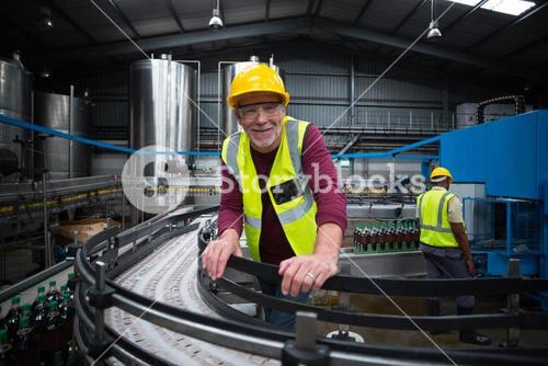 Smiling factory worker leaning on production line