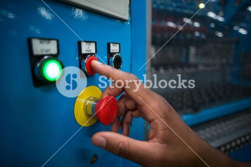 Hands of factory worker pressing a red button on the control board