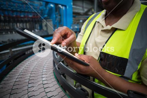 Factory worker using digital tablet in the factory