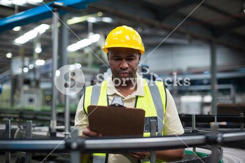Factory worker looking at clipboard in factory