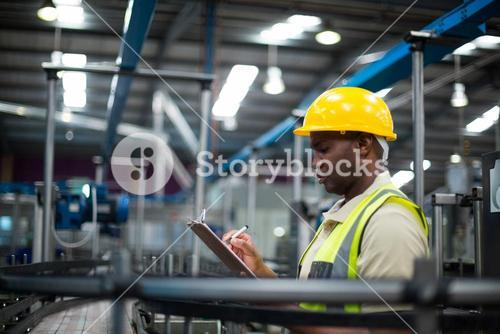 Factory worker writing on the clipboard