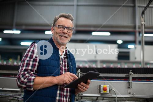 Smiling factory worker using digital tablet in the factory