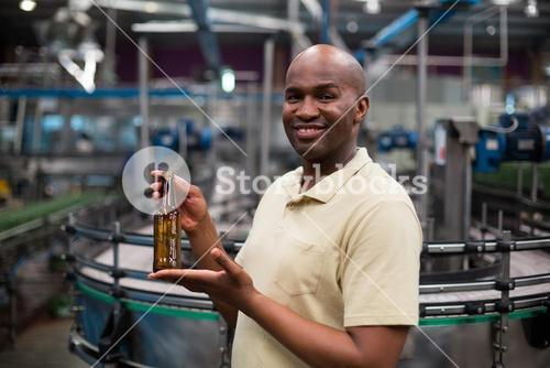 Smiling factory worker holding empty bottle