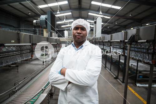 Factory engineer standing with arms crossed in bottle factory