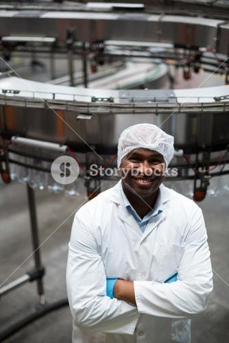Smiling factory engineer standing with arms crossed in bottle factory
