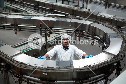 Factory engineer standing next to production line