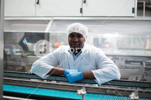 Factory engineer leaning on production line