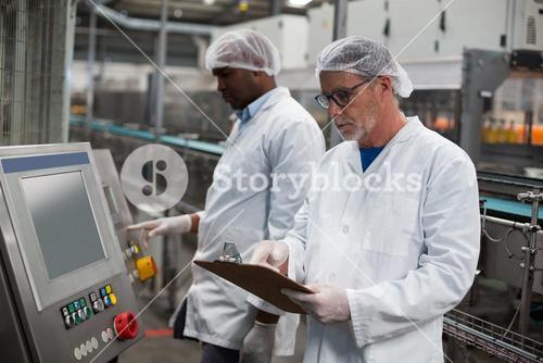 Two factory engineers operating machine in factory