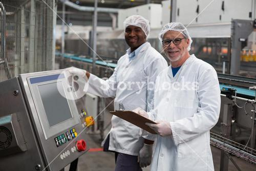 Two factory engineers standing near machine in factory