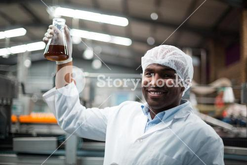 Factory engineers holding a sample of drink