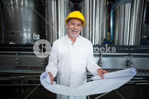 Smiling factory engineer standing in bottle factory with blueprint