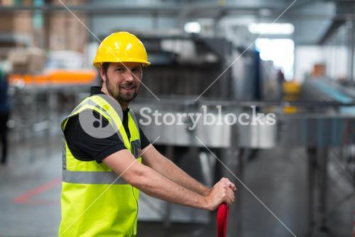 Smiling factory worker pulling trolley in factory