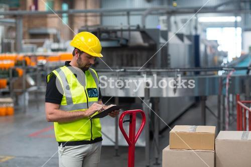 Factory worker using a digital tablet