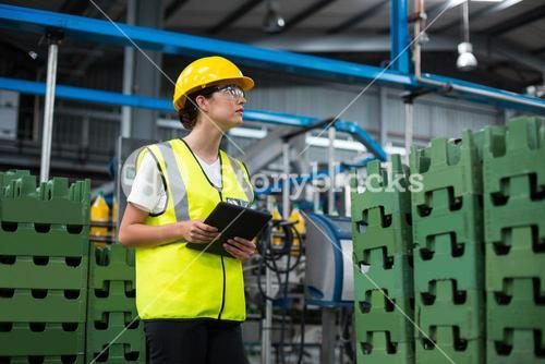 Female factory worker maintaining record on digital tablet