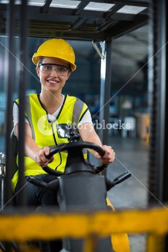 Portrait of smiling female factory worker driving forklift