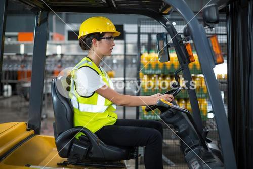 Female factory worker driving forklift