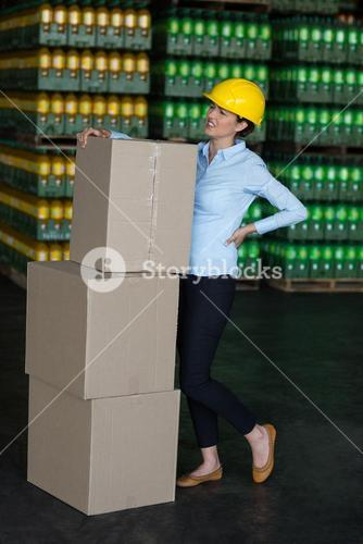 Tensed female worker standing with back pain