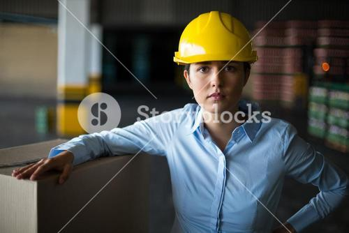 Female factory worker standing with hand on hip in factory