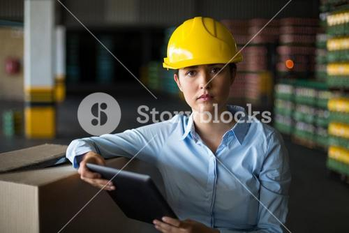 Female factory worker standing with digital tablet in factory