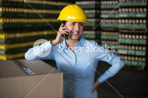 Female factory worker talking on mobile phone