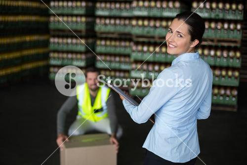 Female factory worker standing with clipboard in factory