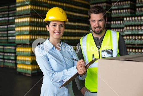 Factory workers maintaining record on clipboard in factory