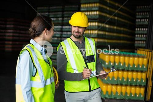Factory workers discussing inventory over clipboard