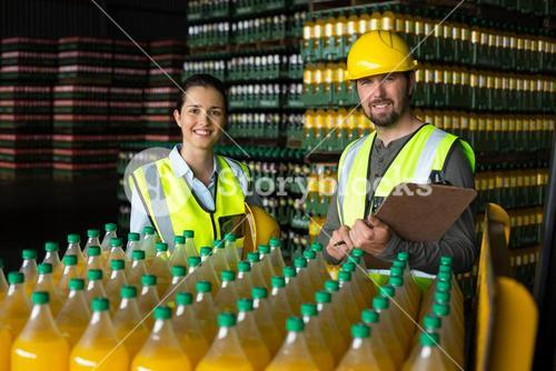 Two factory workers monitoring cold drink bottles