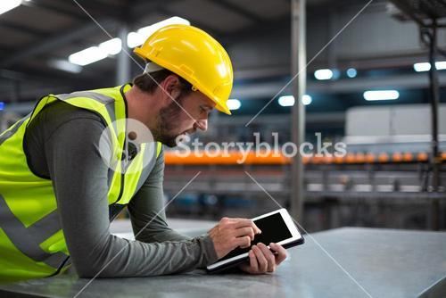Factory worker using digital tablet