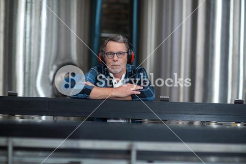 Male factory worker sitting at drinks production factory