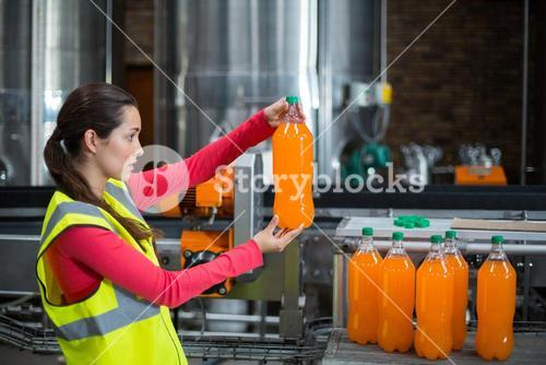 Female factory worker examining a bottle of juice