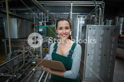 Female factory worker maintaining record on clipboard in factory