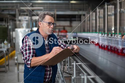 Male factory worker maintaining record on clipboard in factory